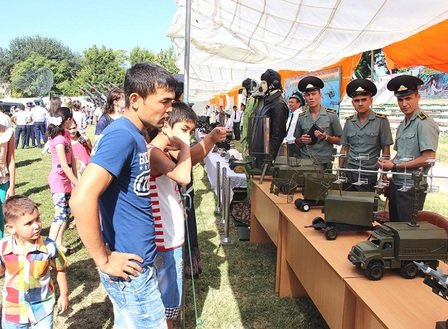 Tashkent residents last August during Uzbekistan's Aviation Day examine models of military vehicles that help protect the country's airspace. [Maksim Yeniseyev]