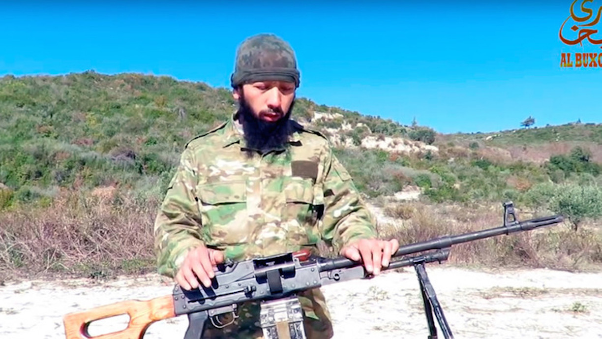An Imam Bukhari Jamaat militant shows off his weapon at an undisclosed location on November 21. [Screenshot by Maksim Yeniseyev of an extremist video.]