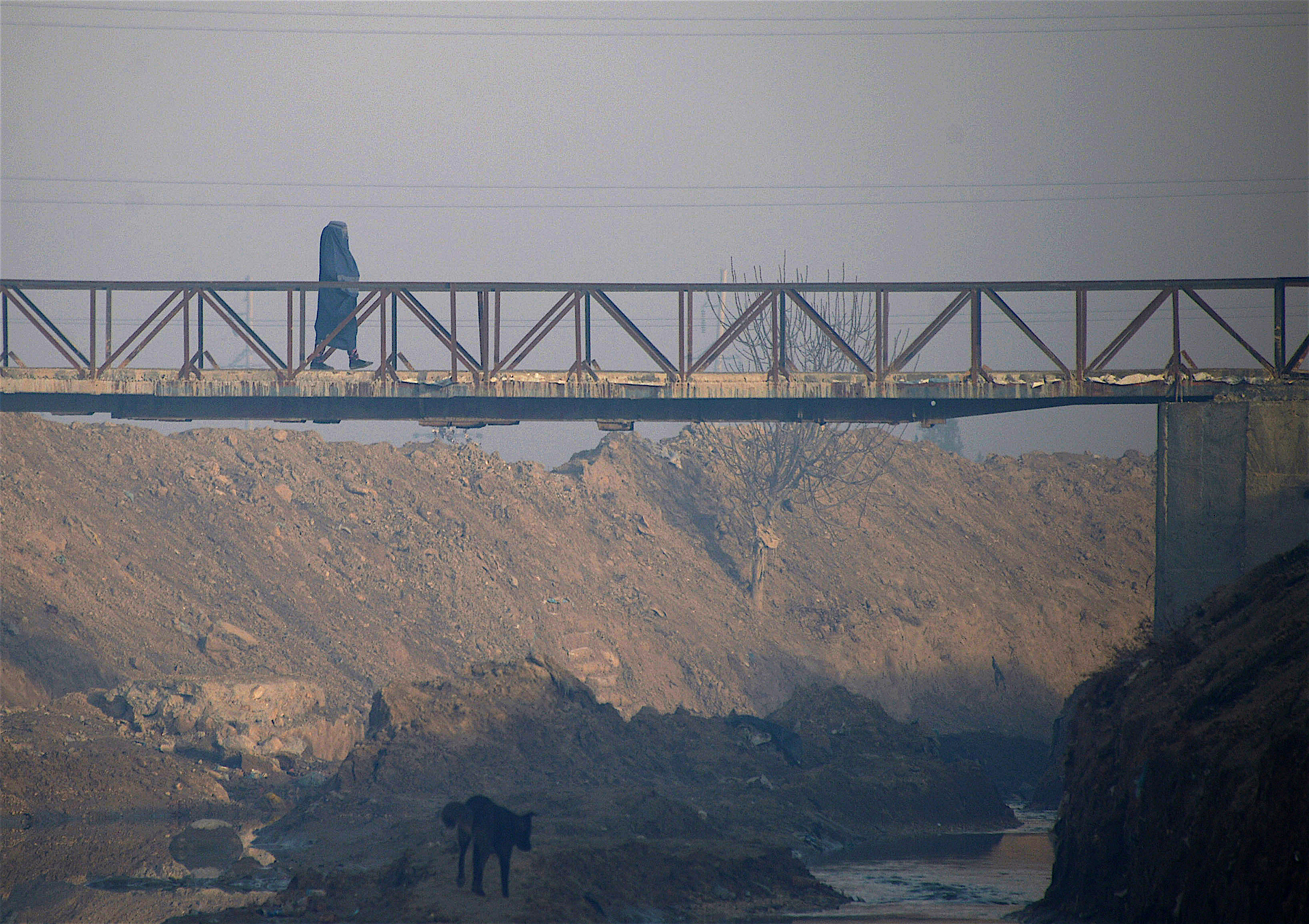 An Afghan woman crosses a bridge in Mazar-i-Sharif on December 3. Mazar-i-Sharif serves as a terminus of a railway connecting Afghanistan and Uzbekistan. [Farshad Usyan/AFP]