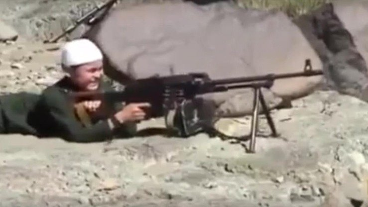 "A boy in Syria fires a machine gun in a ""jihadist"" video that convicted Kazakhstani militant Nurkhan Seytkali posted online in September 2014. The video apparently was filmed in an 'Islamic State of Iraq and the Levant' (ISIL) training camp. [Screenshot by Alexander Bogatik]"