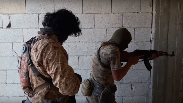 A screenshot of a militant video shows Kyrgyz militants raiding a building in Aleppo in 2016.
