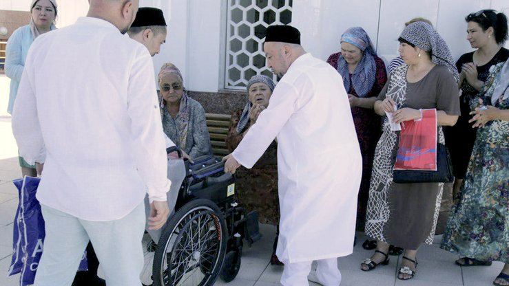 Muslims and an imam give out wheelchairs, bought with donations, to the disabled in Tashkent June 12. [Spiritual Administration of Muslims of Uzbekistan]