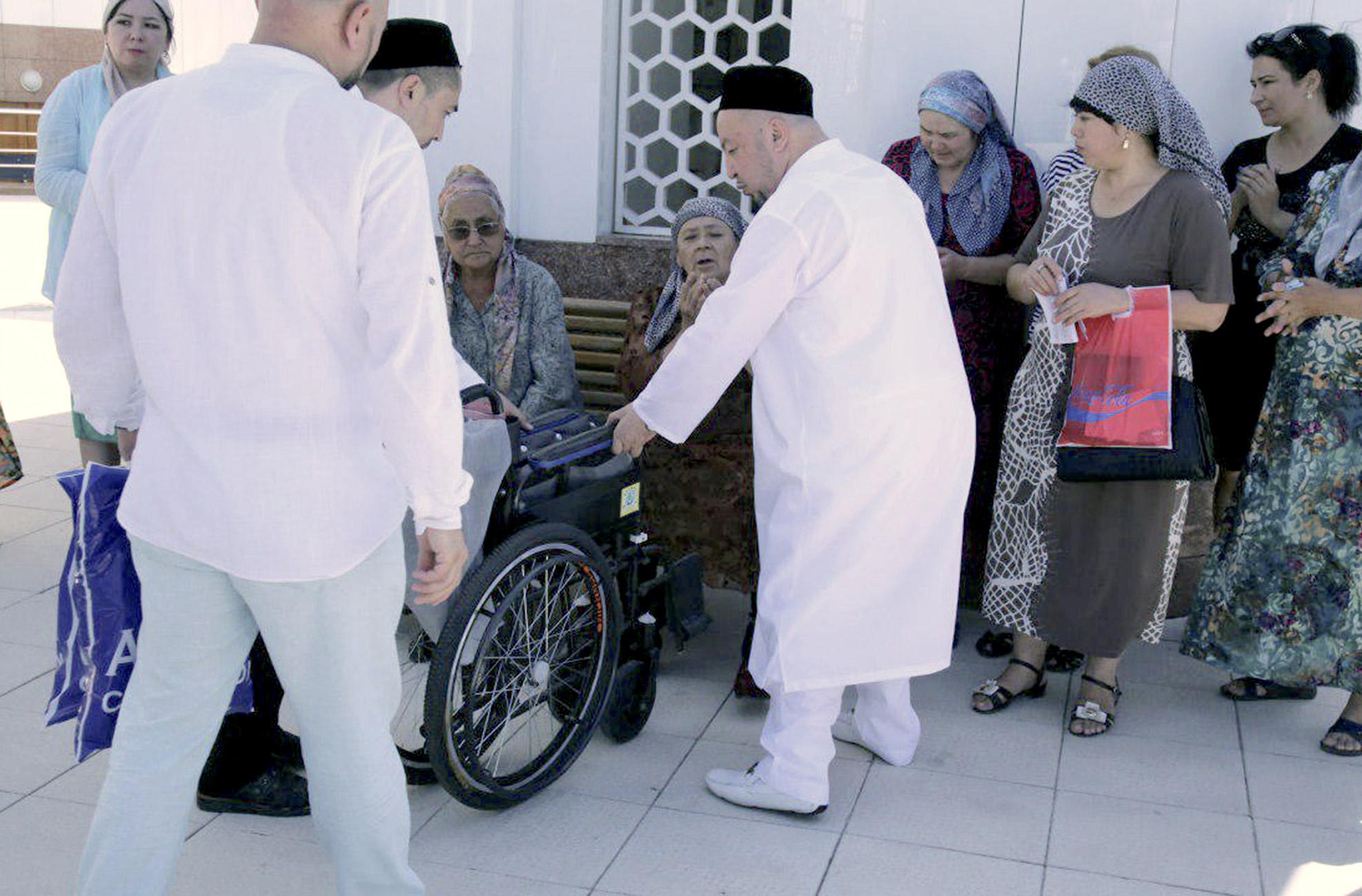Мусульмане вместе с имамом передают нуждающимся купленные на пожертвования инвалидные коляски 12 июня в Ташкенте. [Духовное управление мусульман Узбекистана]