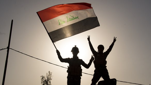 Members of Iraq's federal police force wave Iraq's national flag as they celebrate in the Old City of Mosul on July 9, 2017 after the government's announcement of the liberation of the embattled city from ISIS. [Fadel Senna / AFP]