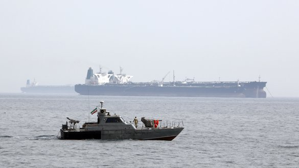 A picture taken on March 12, 2017, shows an Iranian speedboat patrolling as a tanker prepares to dock at an oil facility in the Persian Gulf. Iran's Islamic Revolutionary Guard Corps has used these fast attack boats to disrupt the free flow of commerce and international security. [Atta Kenare/AFP]