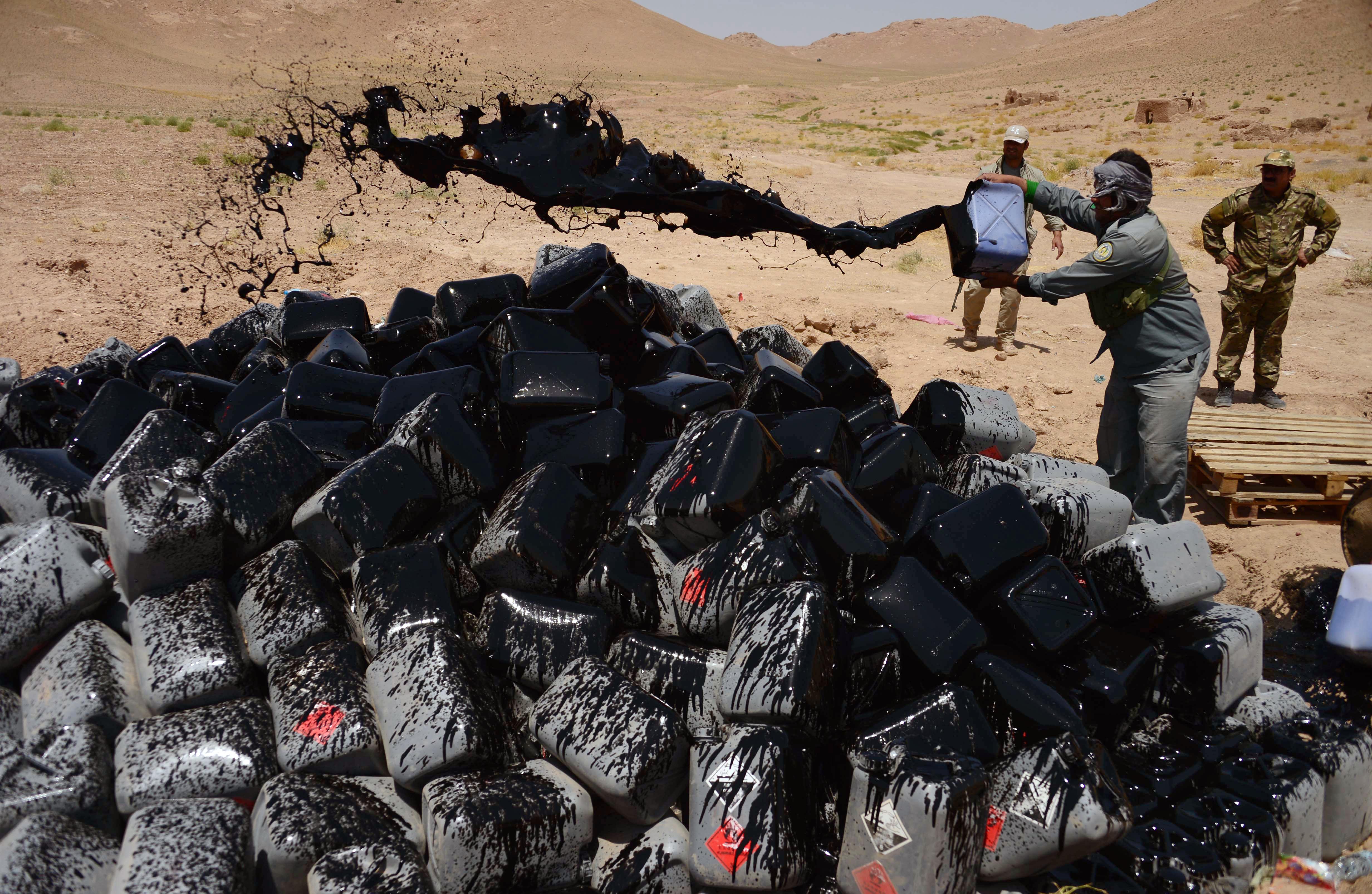 Афганский полицейский льет бензин из канистры на конфискованную уксусную кислоту перед тем, как ее поджечь. Окрестности Герата, 11 июля 2017 г. [Хошанг Хашими/АФП]