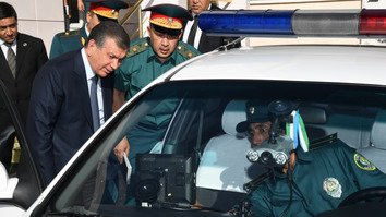 Uzbekistani President Shavkat Mirziyoyev (looking into car) June 29 in Tashkent inspects the camera system inside a traffic police car. The system is part of the Tashkent 'Safe City' project. [Mirziyoyev press office]
