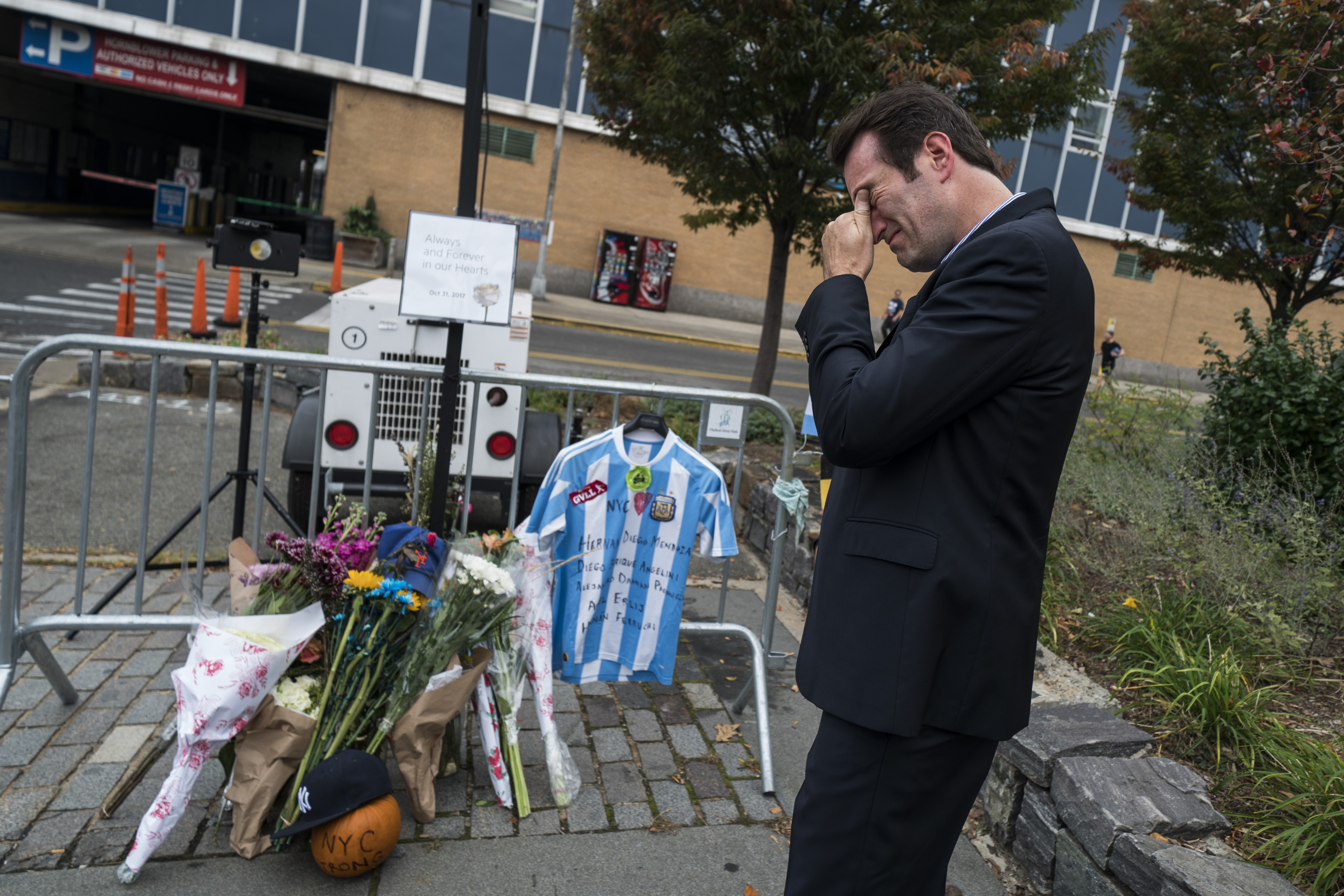 A man places an Argentinian soccer jersey on November 2 at a makeshift memorial for the October 31 terror attack victims in New York. Sayfullo Saipov, the Uzbekistani immigrant suspected in the attack, is accused of killing eight people with a rental truck, including five Argentine men who were celebrating the 30th anniversary of their high school graduation. [Jewel Samad/AFP]