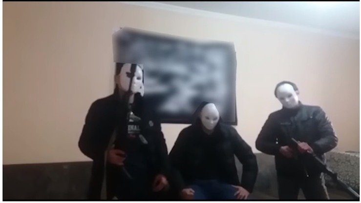 Three masked men pose in front of a flag of the banned Hizb ut-Tahrir group in a propaganda video, urging others to wage armed 'jihad'. Kazakhstani authorities said they arrested those behind the video on November 28, 2017. [YouTube]