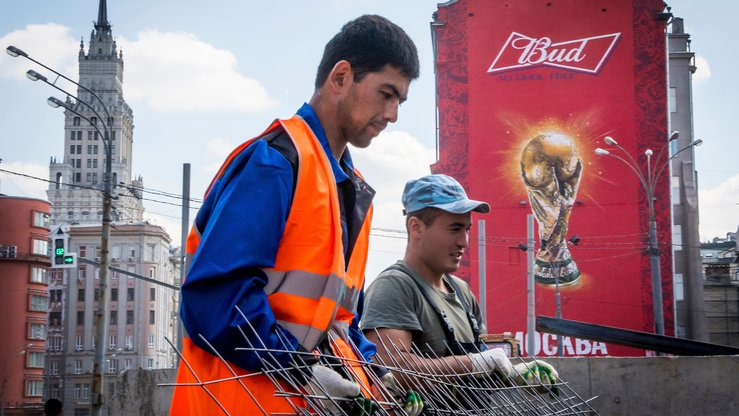 Workers carry steel mesh during street renovation on August 10 in downtown Moscow. Migrants from Central Asia often work in Moscow as street cleaners and construction workers, Farkhod T., 35, of Namangan, Uzbekistan, told Caravanserai. [Mladen Antonov/AFP]