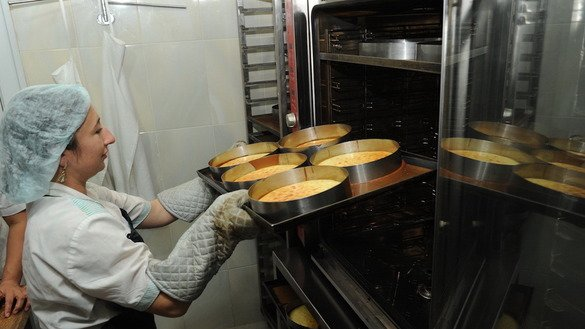 A baker removes pastries from the oven of the Asmar bakery in Almaty in October. The bakery is one of the enterprises founded and owned by businesswoman Asel Bayalinova. Kazakhstani women manage or own almost half of their country's small and medium businesses, according to the European Bank for Reconstruction and Development (EBRD). [Vladimir Tretyakov]
