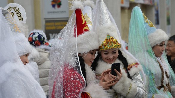 Young women dressed as Snegurochka (Snow Maiden) look at a mobile phone during the New Year's Eve parade in Bishkek December 31, 2015. According to security officials, extremist recruiters in recent years have begun actively using smartphone apps like Telegram and WhatsApp. [Vyacheslav Oseledko/AFP]