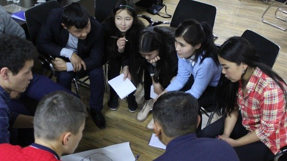 Participants of the simulation game seminar hold group discussions October 19-22 Bishkek. [Institute for Youth Development]