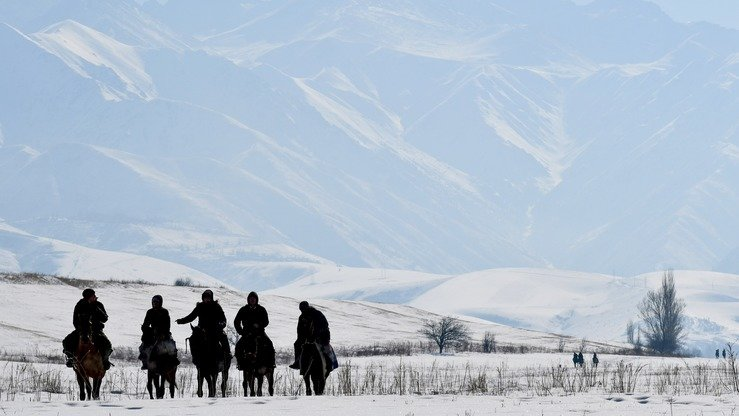 Men ride horseback near Besh-Kungey village, Kyrgyzstan, February 4. Kyrgyzstan's mountains and glaciers provide abundant hydro-power in the summer. [Vyacheslav Oseledko/AFP]