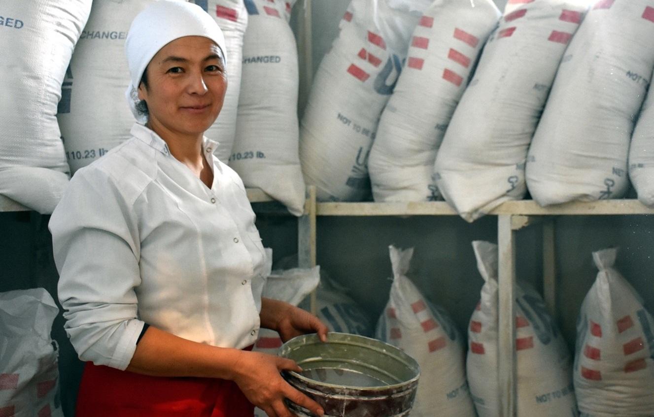 Повар работает в подсобном помещении, в настоящее время заполненном продуктами для школьников. Лейлекский район Баткенской области (Кыргызстан), декабрь 2017 г. [Mercy Corps]