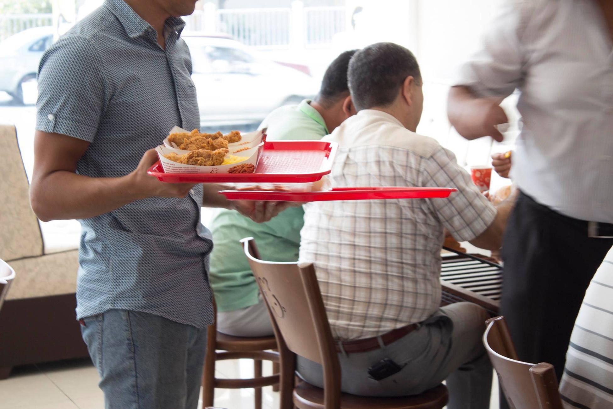 Официант подает жареную курицу в стиле KFC в ресторане. Ташкент, сентябрь 2017 г. Скоро в Ташкенте откроется официальный ресторан этого бренда. [Facebook]