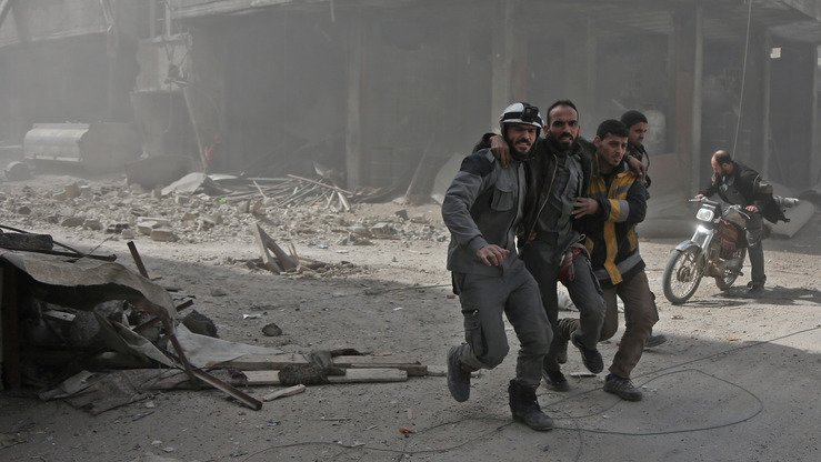 Volunteers from Syrian civil defence help a man during Russia-backed Syrian shelling of opposition-held areas in Eastern Ghouta March 6. [Abdulmonam Eassa/AFP]