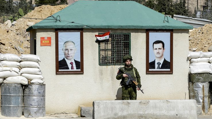 A picture taken March 1 shows a Russian military policeman standing guard between portraits of Syrian President Bashar al-Assad (right) and Russian President Vladimir Putin (left) outside a guard-post at al-Wafideen check-point on the outskirts of Damascus. [Louai Beshara/AFP]