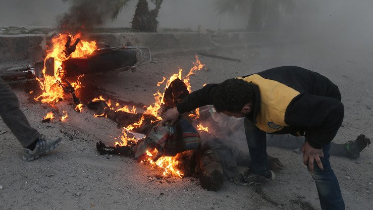 A Syrian civil defence volunteer tries to put out a fire engulfing a man fatally wounded in the bombardment of the rebel-held town of Hamouria, in the besieged Eastern Ghouta region on the outskirts of the capital Damascus, on March 7, 2018. More than 900 civilians have been killed since the Russia-backed regime began its bombing over two weeks ago. [Abdulmonam Eassa/AFP]