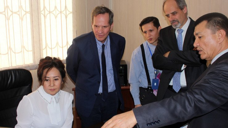 Employees at the Yakkasaray Inter-District Court demonstrate how the E-SUD system works to George Deikun (2nd left), USAID's regional mission director for Central Asia, in Tashkent in 2016. [UNDP]