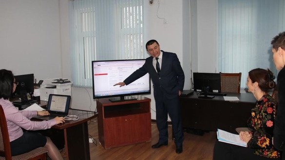 Elyorjon Ismoilov, a judge at the Fergana Inter-District Civil Court, demonstrates the E-SUD system to Helena Fraser (seated at right), UN resident co-ordinator and UNDP resident representative in Uzbekistan in January. [UNDP]