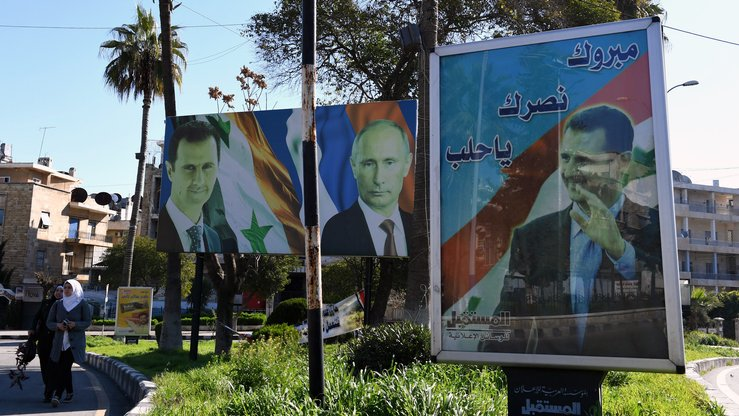 A picture taken March 17 shows portraits of Russian President Vladimir Putin and Syrian President Bashar al-Assad in Aleppo, Syria. [George Ourfalian/AFP]