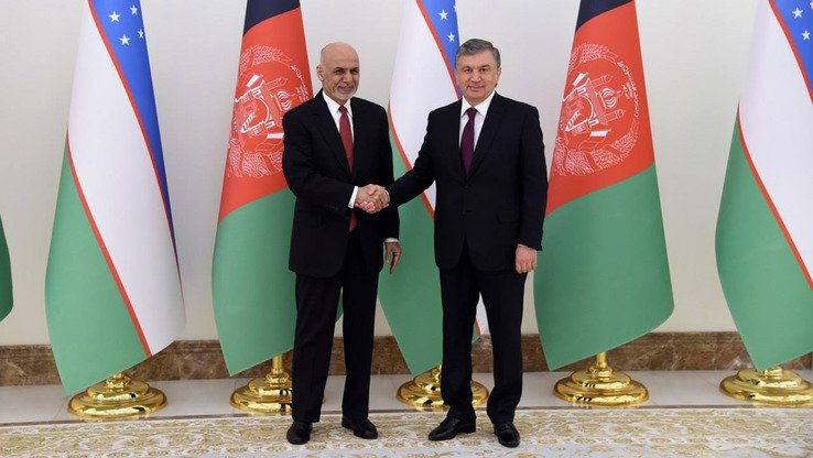 Afghan President Ashraf Ghani (left) and Uzbekistani President Shavkat Mirziyoyev shake hands during an international conference on Afghanistan in Tashkent on March 27, 2018. [Uzbekistani presidential press office]