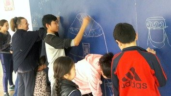 Children at High School No. 21 in Bishkek draw on a chalkboard March 13. Setting aside a space for such creativity is meant to improve the learning environment. [Asker Sultanov]