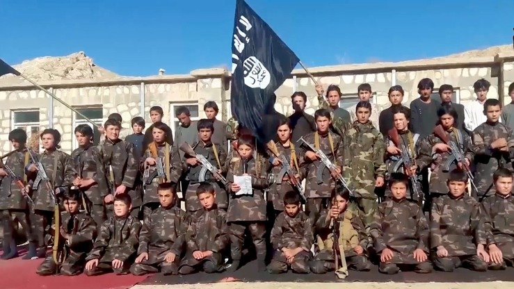 A screenshot from from an IS video released March 4 shows dozens of children, many of them forcibly recruited and brainwashed, armed and brandishing IS's flag. [File]