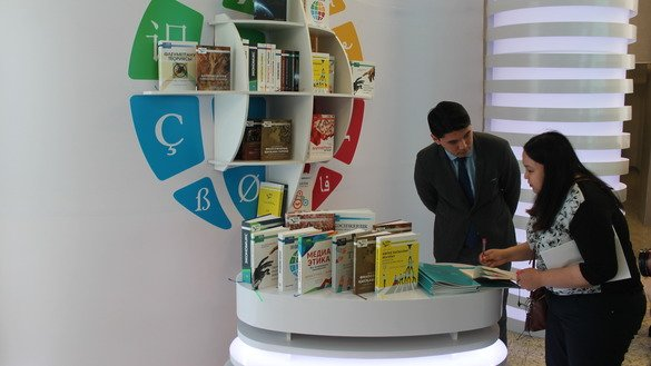 "Alikhan Tuyebai, a project co-ordinator for the ""100 New Textbooks in Kazakh"" project, shows books that have been translated to an exhibition visitor April 14 in Astana. [Aydar Ashimov]"
