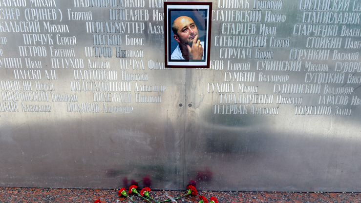 Flowers lie under a picture of 41-year-old anti-Kremlin reporter Arkady Babchenko on the memorial wall of Moscow's journalists' house in Moscow on May 30. The prominent journalist was reported to have been murdered May 29 in an apparent contract-style killing in the stairwell of his building in Kyiv. A day later, Ukrainian officials announced Babchenko's murder was staged in order to foil a real assassination attempt against him orchestrated by Russia. [Vasily Maximov/AFP]