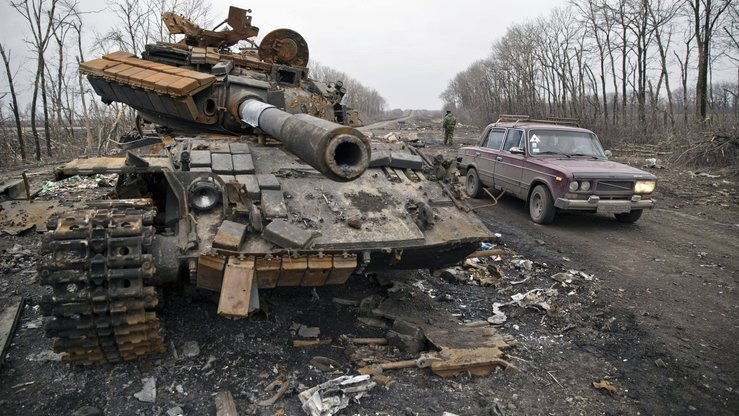 A car passes a destroyed tank outside Chornukhyne, Ukraine, on March 2, 2015, after Russia-backed forces overran a former Ukrainian army checkpoint. [File]