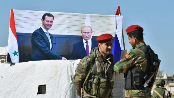 Syrian soldiers talk next to a poster of Russian and Syrian leaders at Abu al-Duhur crossing, as displaced families return from opposition-held areas in Idlib province to their villages in regime-controlled territory on April 4th. [George Ourfalian/AFP]