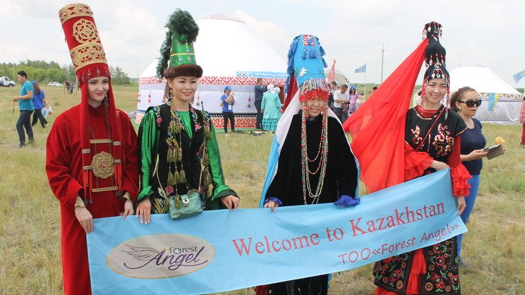 Female members of various nationalities welcome tourists to the festival. [Aydar Ashimov]