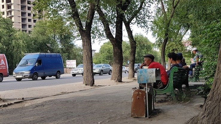 Men from poor Kyrgyz villages on June 30 sit on a bench in Bishkek, waiting for offers of temporary work like repairs, construction or unloading of carts. Most Kyrgyz prefer to look for work in the capital rather than going to Russia, where life for migrants is worsening every day. [Arman Kaliyev]