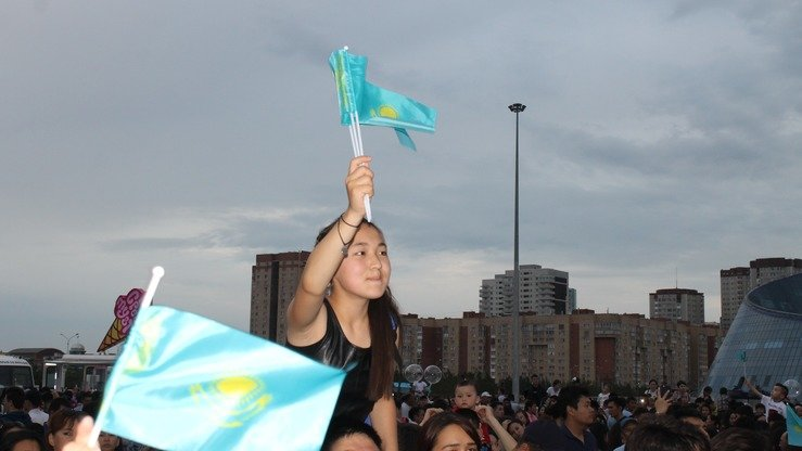 A girl waves a Kazakh flag above a crowd of revelers. [Aydar Ashimov]