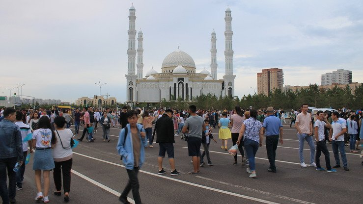 Astana's central mosque is seen in the distance as scores of Kazakhs stroll down the street. [Aydar Ashimov]