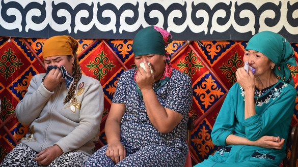 Relatives of Burulai Turdaaly Kyzy weep as they hold a ceremony June 28 in Sokuluk, marking 40 days since she was murdered in a Chui Province police station by her alleged kidnapper. [Vyacheslav Oseledko/AFP]