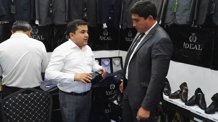 Akram Karimov (left), director of Ideal, an Uzbek shoe manufacturer, talks with visitors at the Sughd 2018 international trade fair in Khujand on July 6. [Negmatullo Mirsaidov]
