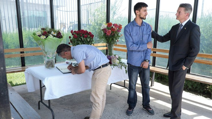 US Charge d'Affaires Kevin Covert (R), at the US Embassy in Dushanbe on July 31, speaks with a man as people come to pay tribute to the victims of the IS-claimed attack days earlier that left four tourists dead, including two Americans. [STR / AFP]