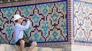 A tourist photographs an ornate wall in Samarkand in July. [Courtesy of Uzbek State Committee for Tourism Development]