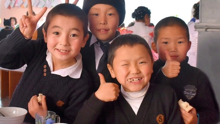 "Kyrgyz children smile after a hearty meal at school in Leilek District, Batken Province, last December. The main goal of Take My Child to School campaign is ""the realisation of the right of every child to education"", the organisers say. [Mercy Corps]"