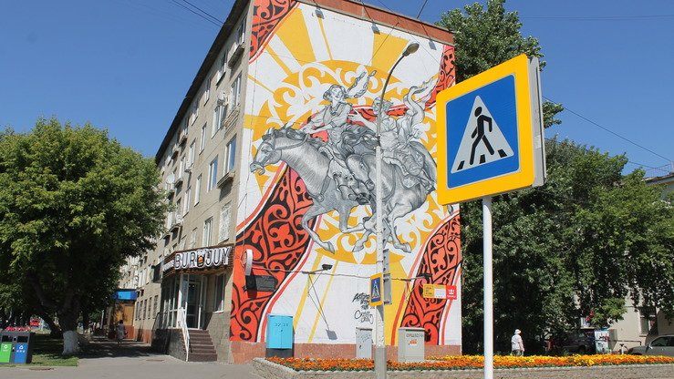 "This mural, seen behind an Astana crosswalk August 14, depicts the Kazakh game of kyz kuu (""girl chasing""). A young man pursues a beauty. Both are on horseback. [Aydar Ashimov]"