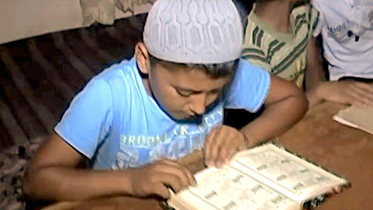 Ученик изучает Коран в незаконной исламской школе. Скриншот с узбекского официального телеканала.