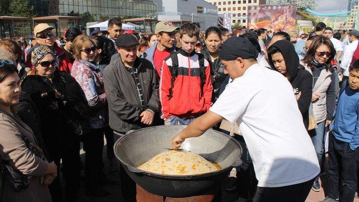 Посетители узбекского гастрономического фестиваля наблюдают за поваром, который готовит узбекский плов, прежде чем они отведают блюдо. Астана, 8 сентября. [Айдар Ашимов]