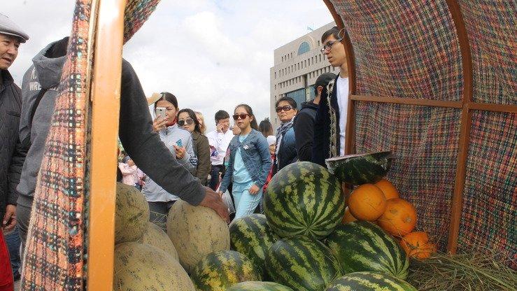 Посетители наслаждаются бесплатными образцами вкусных дынь из Ташкента. Некоторые покупают и забирают домой. Астана, 8 сентября. [Айдар Ашимов]
