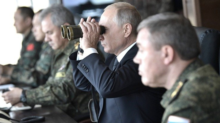 Russian President Vladimir Putin raises a pair of binoculars to observe the Vostok-2018 military drills September 13. [The Kremlin]