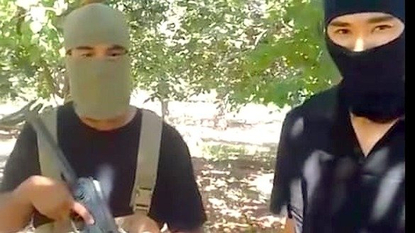Two masked militants are shown in a screenshot from a video posted on YouTube September 8. The pair vowed vengeance for Kazakhstan's ban on hijabs in school. [Screenshot by Gulnaz Razdykova]