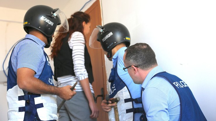 "Police officers prepare to ""raid"" a brothel holding enslaved women as part of an exercise in Koshi September 27. A policewoman pretends to be a neighbour so that suspects will open the door. [Aydar Ashimov]"