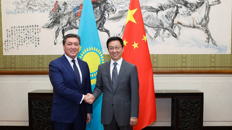 Chinese Vice Premier Han Zheng (right) shakes hands with Kazakh First Deputy Prime Minister Askar Mamin in Beijing September 25. Allegations of humans rights abuses against ethnic Kazakhs in China are testing Astana's relationship with Beijing. [Lintao Zhang/AFP]